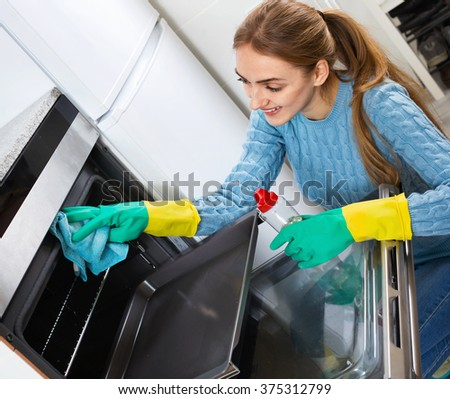 Smiling positive adult girl in gloves removing snuff in oven  - stock photo