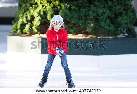 smiling positive boy enjoying ice skating at outdoor skating rink with christmas tree in the background, winter holiday or vacation activity - stock photo