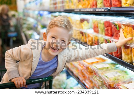 smiling positive boy grocery shopping at the supermarket sitting in the cart helping his mother - stock photo