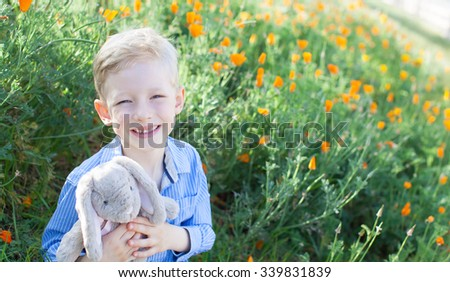 smiling positive boy holding easter bunny enjoying spring time at the field of blooming california orange poppies - stock photo