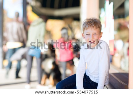 smiling positive boy sitting at outdoor shopping mall with other people in the background enjoying the time
