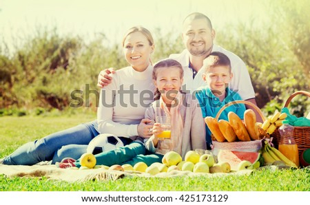 Smiling positive cheerful family of four having a picnic outdoors in a sunny weather - stock photo