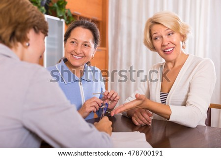 Smiling positive female pensioners signing documents at bank with agent