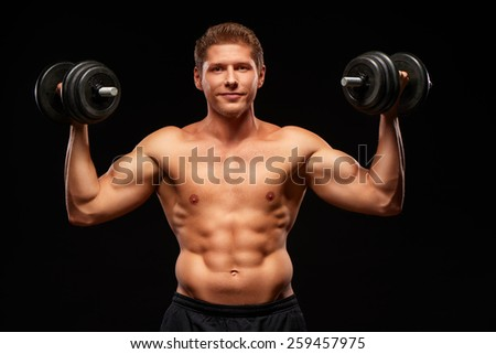 Smiling powerful shirtless muscular sportsman pumping biceps muscles with black dumbbells, dressed in black shorts, looking at camera, isolated on black background - stock photo