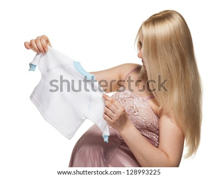 Smiling pregnant woman choosing clothes for newborn; isolated on white - stock photo