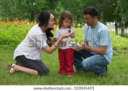 Smiling pregnant woman,  her husband and little daughter