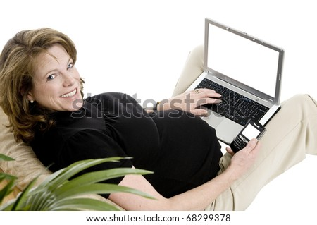 smiling pregnant woman in her 40's, with laptop, and phone, casual clothing, blank screens - stock photo