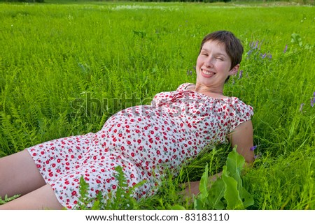 Smiling pregnant woman lie on the grass - stock photo