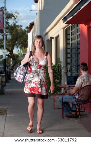Smiling pregnant woman walking down the street - stock photo