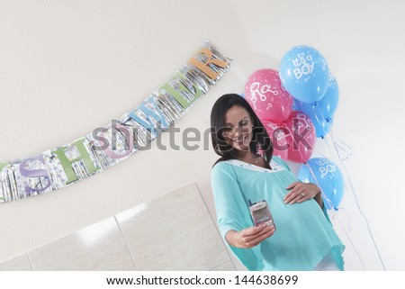 Smiling pregnant woman with her new baby monitor at baby shower - stock photo