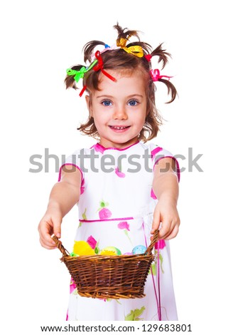 Smiling preschool girl holding wicker basket with Easter decoration - stock photo