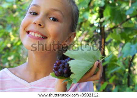 Smiling preteen girl with grapes on grapevine background - stock photo
