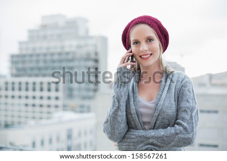 Smiling pretty blonde on the phone outdoors on urban background - stock photo