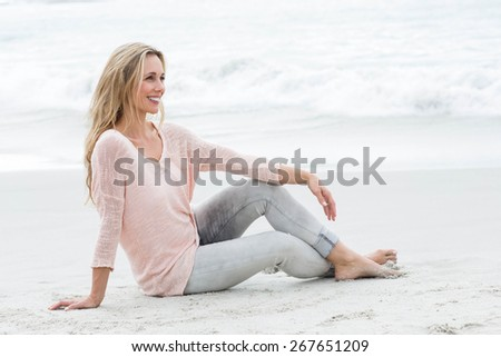 Smiling pretty blonde relaxing on the sand at the beach