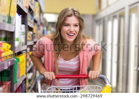 Smiling pretty blonde woman buying a products in supermarket - stock photo