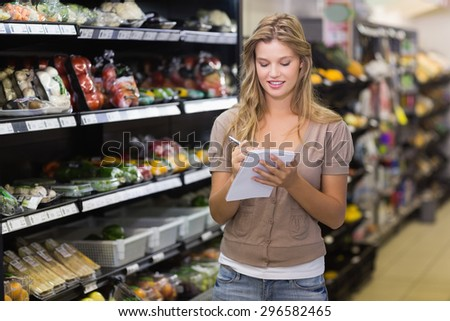 Smiling pretty blonde woman writing on his notepad at supermarket