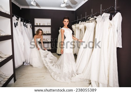 Smiling pretty bride chooses white gown at shop of wedding fashion - stock photo