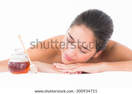 Smiling pretty brunette on massage table with white backgroung - stock photo