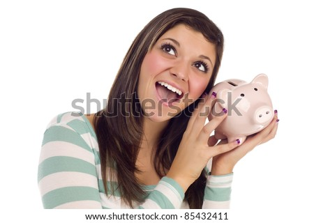 Smiling Pretty Ethnic Female Daydreaming and Holding Pink Piggy Bank to Her Ear Isolated on a White Background. - stock photo