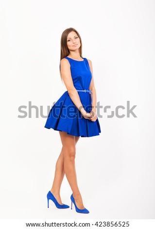 Smiling pretty girl in blue dress, studio full length portrait - stock photo