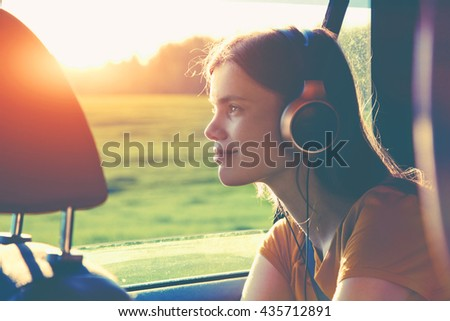 smiling pretty girl listening to music with headphones moving in car - stock photo