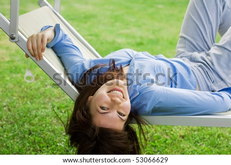 Smiling Pretty Girl Lying On A Deckchair - stock photo