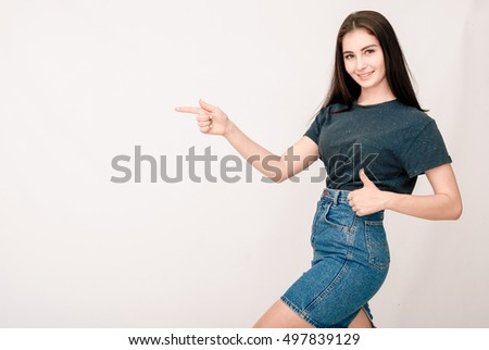 Smiling pretty girl pointing on blank copy copy space for product or text and making thumb up gesture