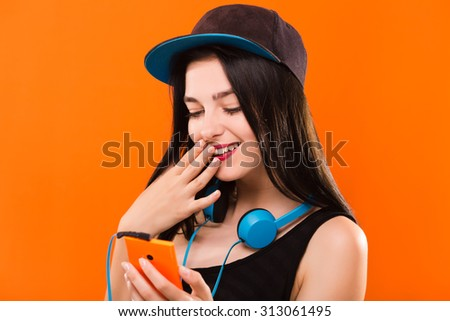 Smiling pretty girl, with blue headphones on her neck, wearing in black blouse and cap, holding smart phone in her hand - isolated on orange background, in studio, waist up - stock photo