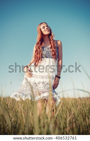 Smiling pretty hippie woman standing in the meadow - stock photo