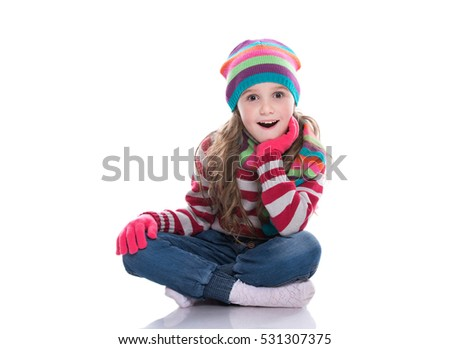 Smiling pretty little girl wearing colorful knitted scarf, hat and gloves isolated on white background