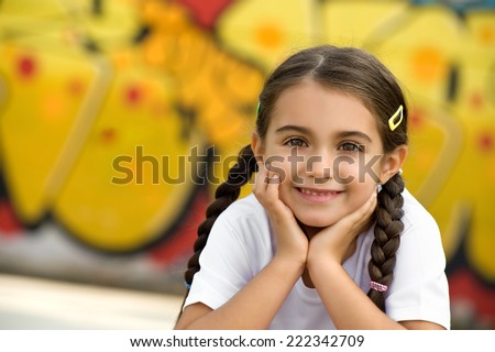 Smiling Pretty Little Girl with Braided Hair Putting Both Hands on Face, Looking at Camera - stock photo