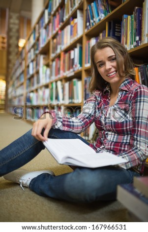 Smiling pretty student sitting on library floor holding book in college