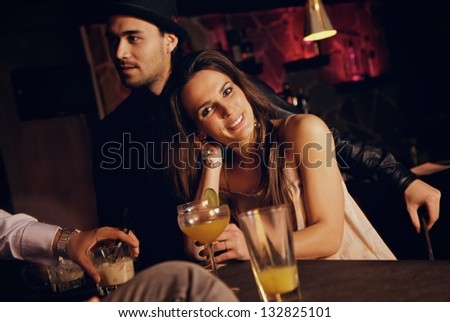 Smiling pretty woman at the bar enjoying with her friends