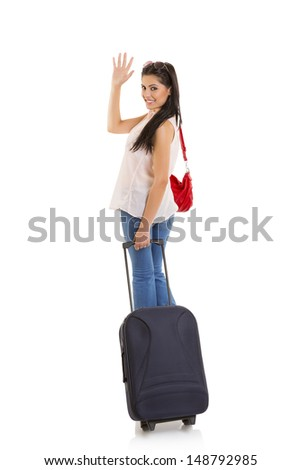 Smiling pretty woman carrying travel suitcase and waving goodbye. Isolated on white. - stock photo