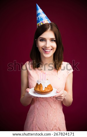 Smiling pretty woman holding cake with candles over pink background. Looking at camera. Celebrating her birthday! Wearing in pink dress - stock photo