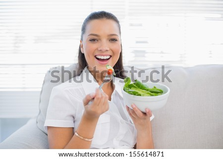 Smiling pretty woman holding healthy salad sitting on sofa in bright living room