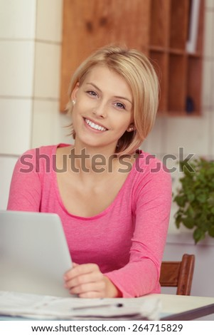 Smiling pretty woman in a pink top sitting at a table working at home in her living room looking at the camera with a beaming smile