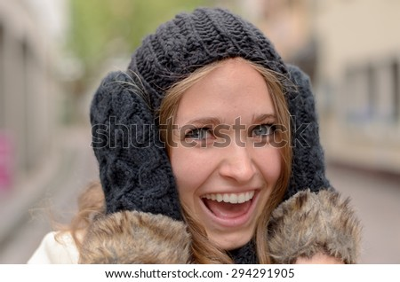 Smiling pretty woman in winter fashion wearing warm knitted woollen gloves and hat holding her hands to her ears and grinning playfully at the camera - stock photo