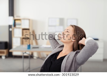 Smiling Pretty Woman Leaning her Back on a Chair with Hands her Head While Relaxing in the Office During her Break Time. - stock photo