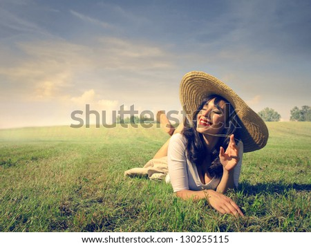 smiling pretty woman lying on the grass - stock photo