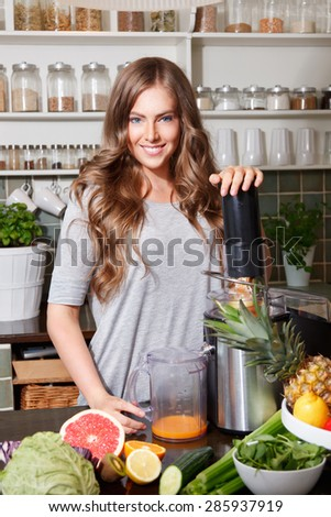 Smiling pretty woman making healthy juice - stock photo
