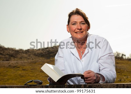 Smiling pretty woman middle aged reading a book and enjoying outdoors. Clear sunny spring day with blue sky. - stock photo