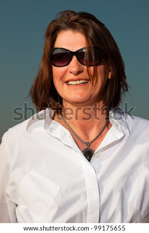 Smiling pretty woman middle aged wearing sunglasses enjoying outdoors. Clear sunny spring day with blue sky. - stock photo
