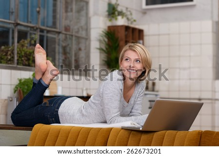 Smiling pretty woman relaxing with her laptop lying on the dividing wall in her living room with her bare feet in the air smiling as she looks to the side - stock photo