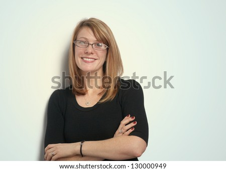 Smiling pretty woman with glasses leaning against wall - stock photo