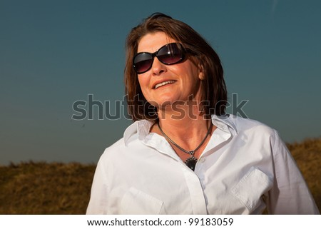 Smiling pretty woman with sunglasses middle aged enjoying outdoors. Clear sunny spring day with blue sky. - stock photo