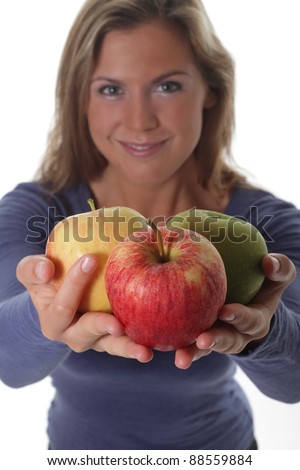 Smiling pretty women holds three different apples in her hands and offers them up - stock photo