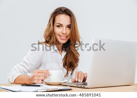 Smiling pretty young businesswoman drinking coffee and working with laptop over white background