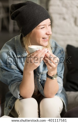 Smiling pretty young girl with cup of coffee