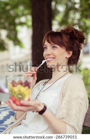 Smiling Pretty Young Lady Eating Fresh Fruit Salad on a Plastic Container While Sitting on the Bench and Looking Into Distance. - stock photo